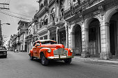 Vintage classic red american oldtimer car in old town of Havana Cuba on black and white background