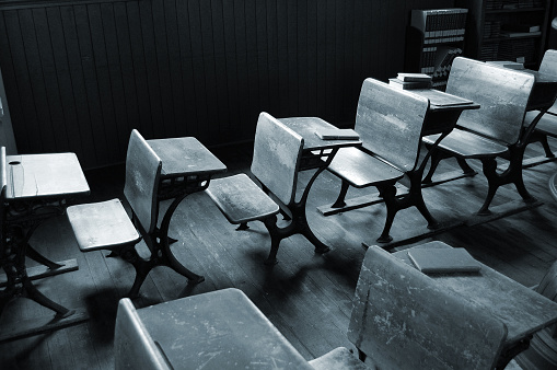 Old classroom student  desks in a rural one room schoolhouse... Black and White with blue tint.