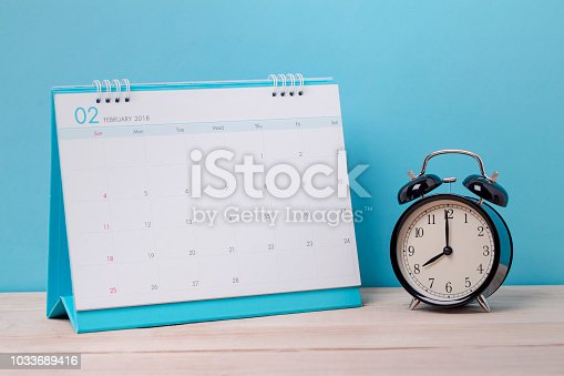 istock Vintage clock and calendar February on wood, time concept 1033689416