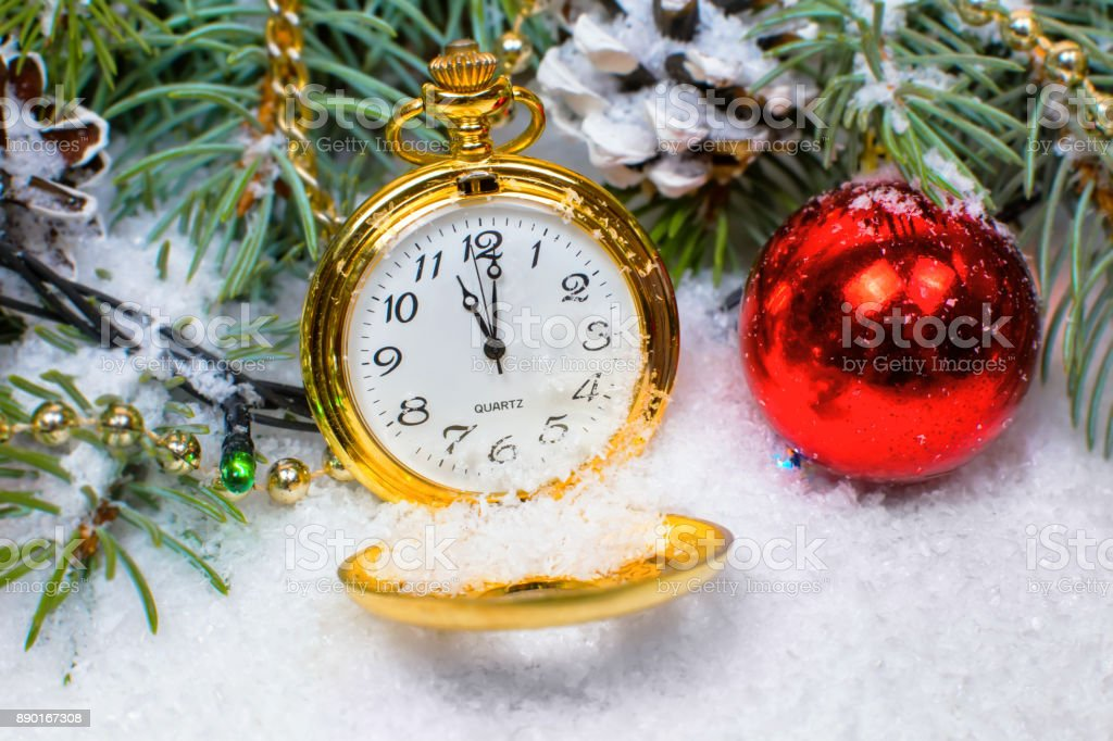 A vintage clock in the snow against the background of a Christmas tree and a garland stock photo
