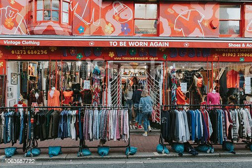 BRIGHTON, ENGLAND - October 24th, 2018: Vintage clothing shop facade with a lot of clothes in the street, and people entering inside it.