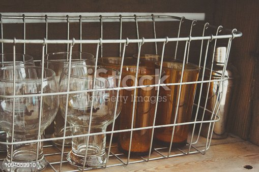 A vintage drink bar stocked with a martini shaker and glasses on wooden crates.