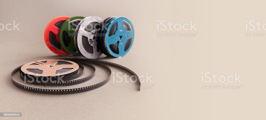 Vintage collection 8 mm cinema film reel. Retro design colorful celluloid accessories for home video projector. Gray background, selective focus stock photo