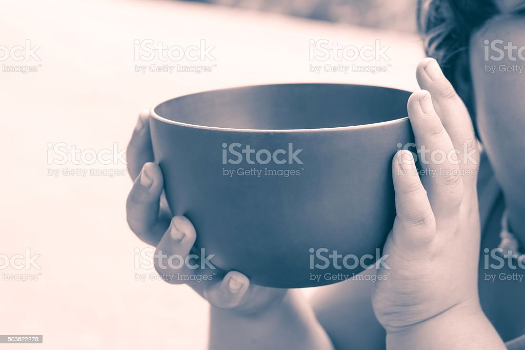 vintage color of a hungry children holding an empty bowl stock photo