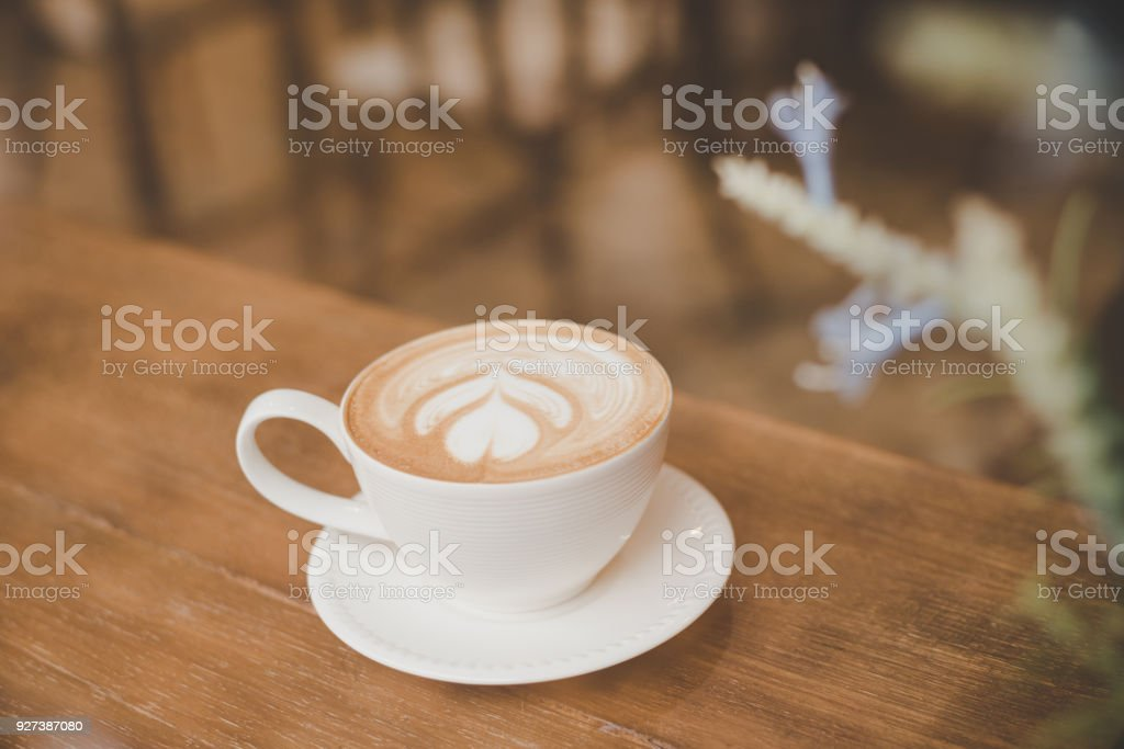 Vintage color tone of coffee latte art on wooden table in coffee shop.