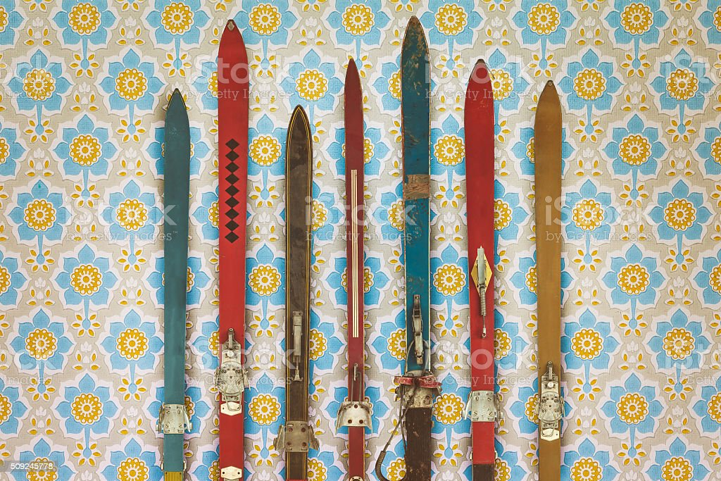 Vintage Colorful Used Skis In Front Of Retro Wallpaper Royalty Free Stock Photo