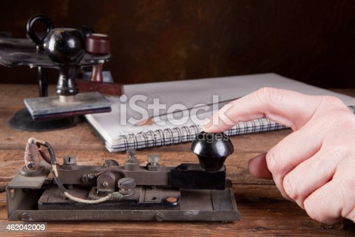 Hand tapping morse code on an antique telegraph machine