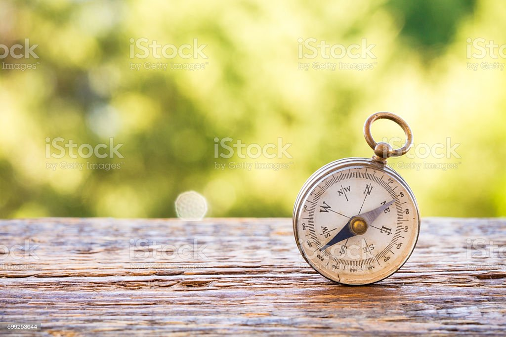 Vintage compass on wooden table and bokeh background stock photo