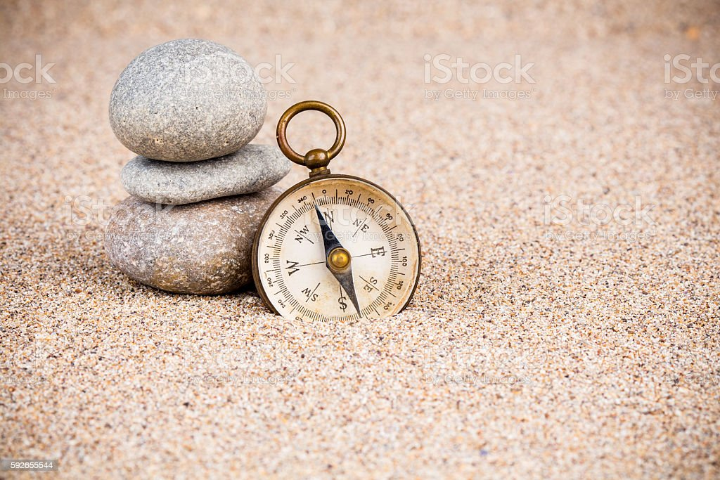 Vintage compass with pebble stones on sand stock photo