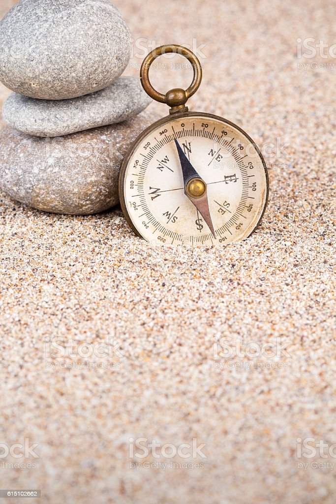 Vintage compass with three pebble stones portrait view stock photo