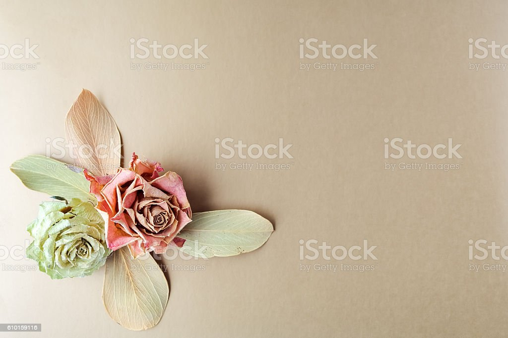 Vintage composition dry bouquet with roses on gold background. Backdrop stock photo