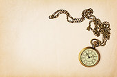 Vintage composition with bronze pocket watch on a chain on yellowed paper background