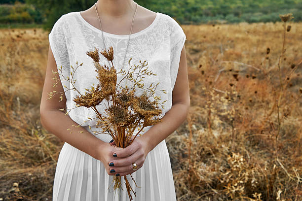 vintage concept with a young woman holding a bouquet - hipster braut stock-fotos und bilder