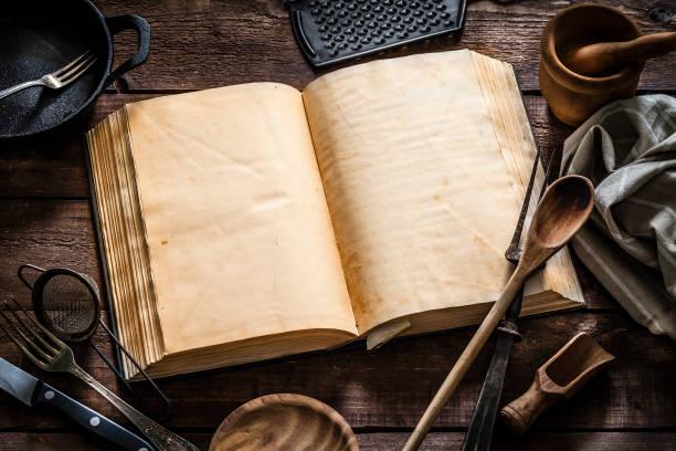 Vintage cookbook with kitchen utensils stock photo