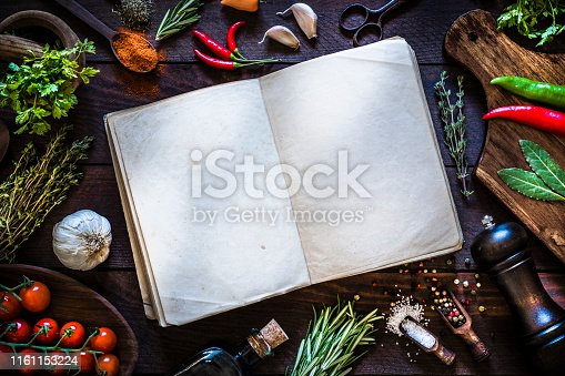 Top view of a vintage open cookbook surrounded by some spices and herbs like thyme, rosemary, laurel, pepper, garlic and chervil, and some kitchen utensils. The cookbook is at the center of the image and its pages are empty so you can use it as a useful copy space. Objects are on a rustic dark brown wooden table. Low key DSLR photo taken with Canon EOS 6D Mark II and Canon EF 24-105 mm f/4