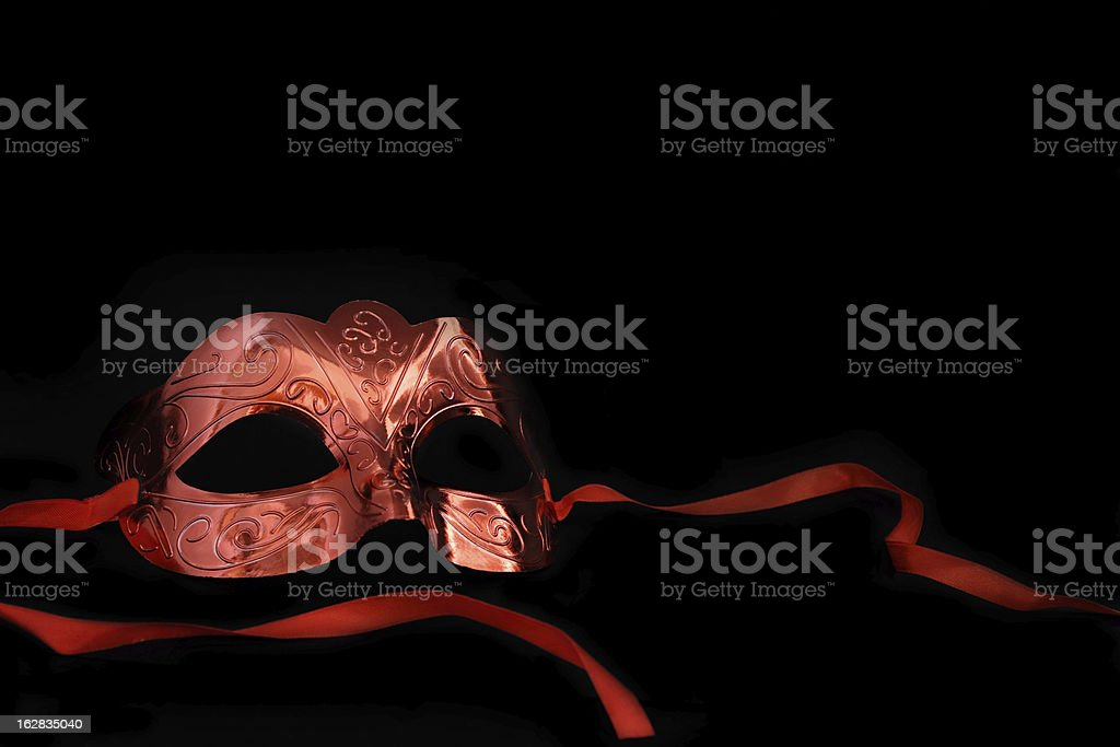 Vintage copper colored carnival mask on a black background stock photo