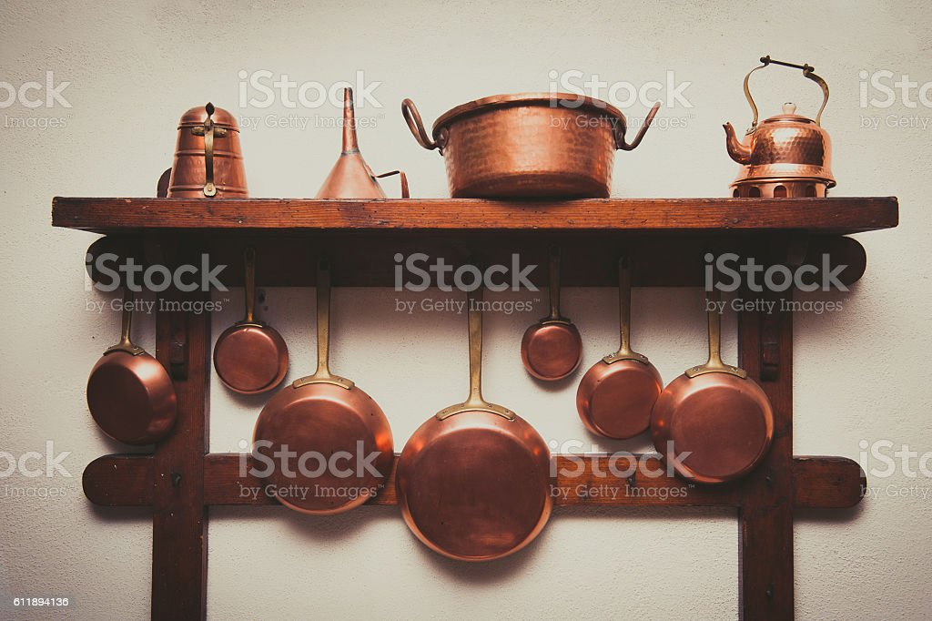 Vintage copper cookware collection on wooden shelf stock photo