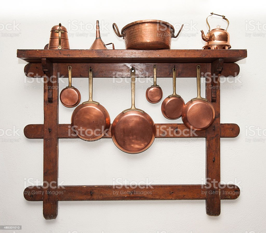 Vintage copper cookware hung on wooden shelf stock photo