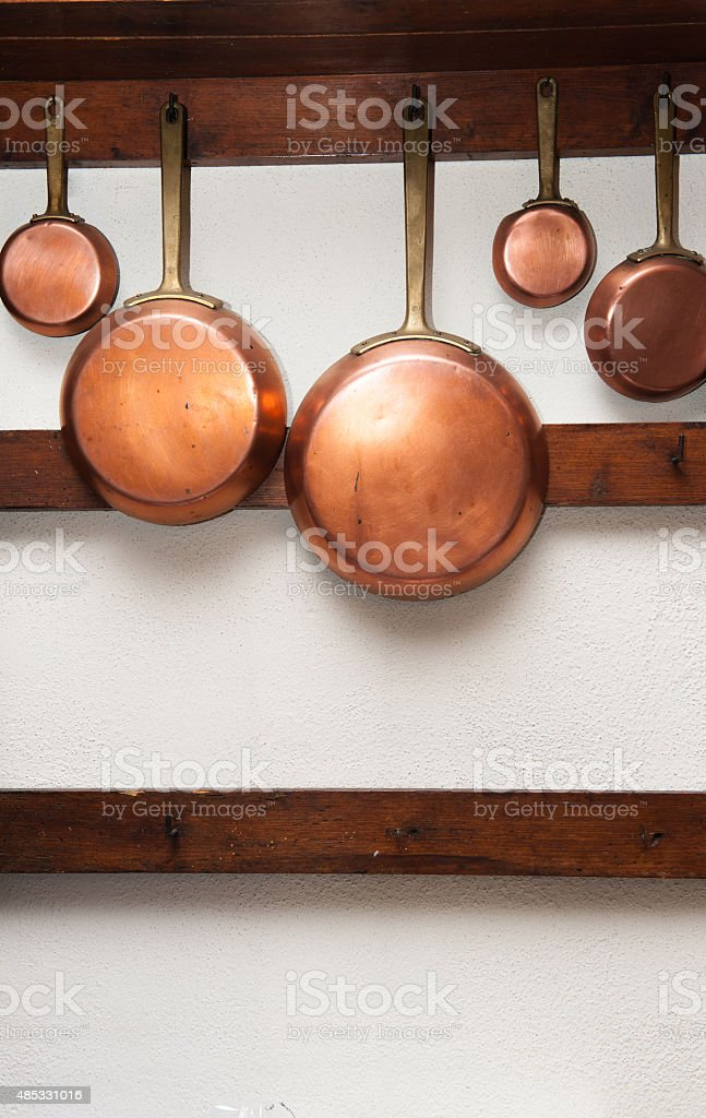 vintage copper pans hung on wooden shelf stock photo