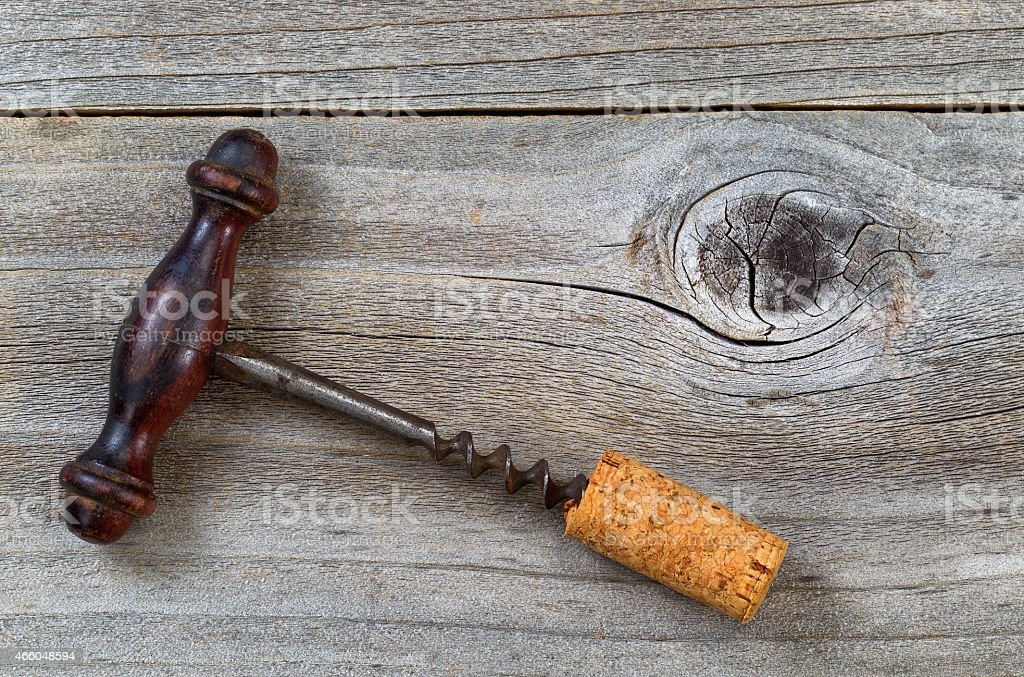 Vintage Corkscrew with attached cork on rustic wood stock photo
