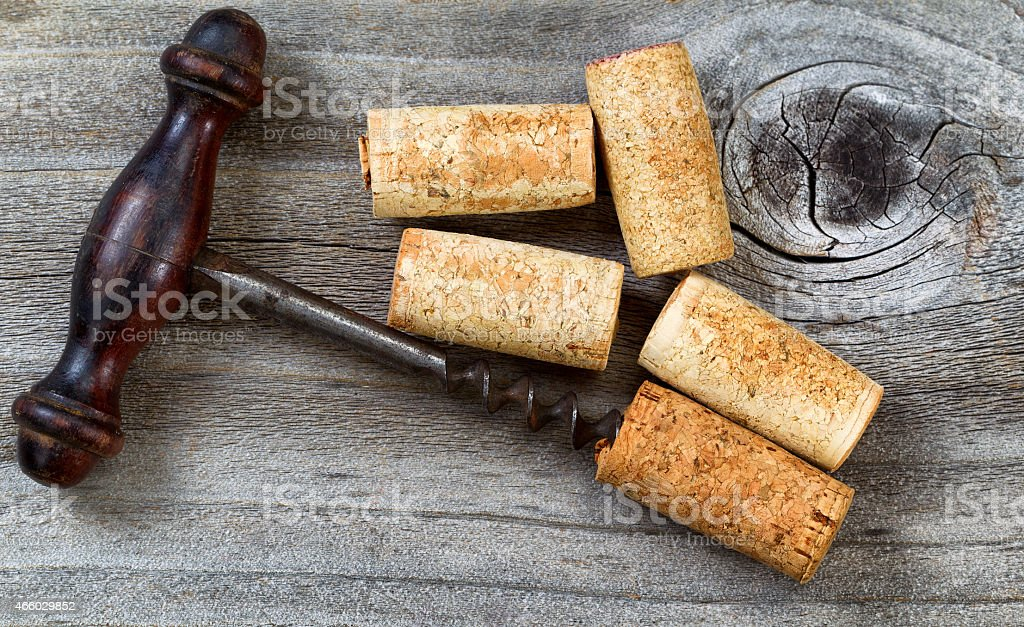Vintage Corkscrew with used corks on aged wood stock photo