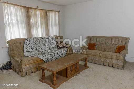 Vintage couches and coffee table left forgotten in an abandoned house in the deep south