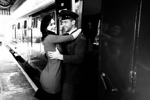 Vintage couple embracing and laughing on railway station platform as train arrives stock photo