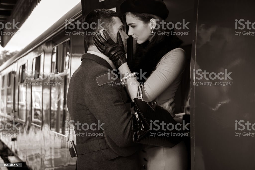 Vintage couple embracing on railway station platform as train is about to depart stock photo