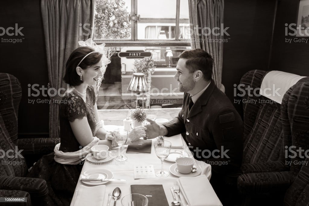 Vintage couple holding hands over table of train carriage stock photo