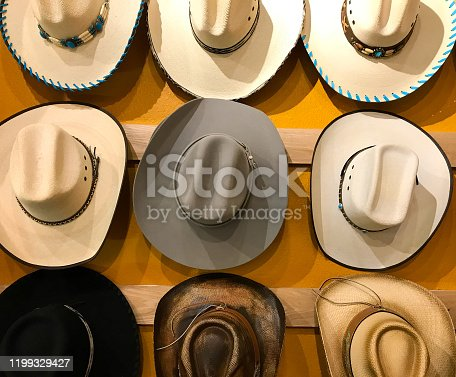 Vintage Cowboy Hats Hanging, Vibrant Yellow Background