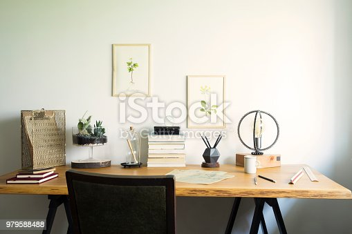 istock Vintage, creative home office interior with wooden desk, books, laptop, romantic illustrations of plants, lamp and office accessories. 979588488