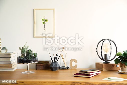 istock Vintage, creative home office interior with wooden desk, books, notebooks, romantic illustrations of plants, table lamp and office accessories. Stylish space for freelancer. 979588426