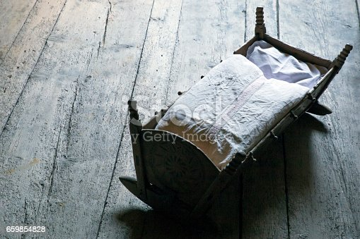 A wooden vintage crib (child bed) with carvings and white linnen, resting on an old worn wooden floor.