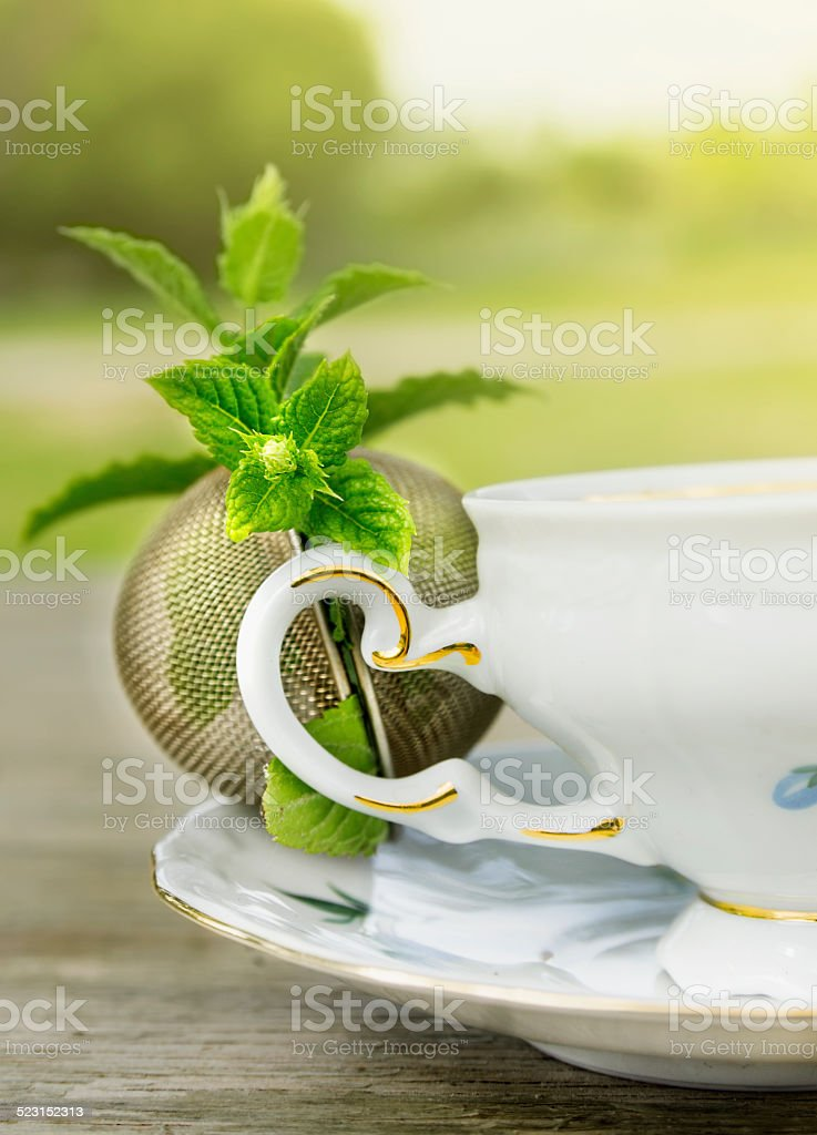 Vintage cup with Peppermint  and tea strainer  on garden table stock photo