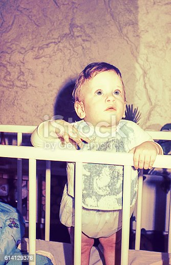 Vintage photo of a cute little boy in his cradle looking above