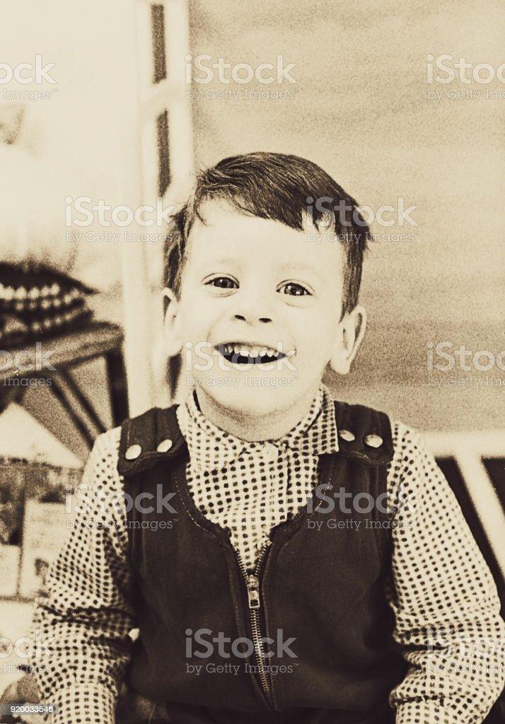 Vintage cute toddler laughing at camera stock photo