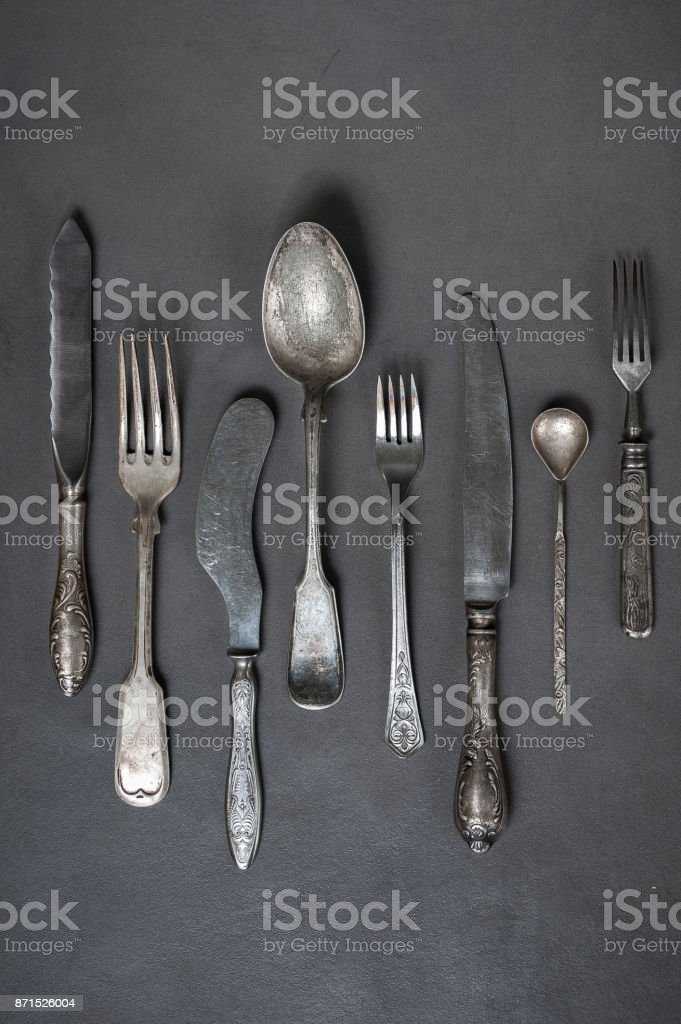 Vintage cutlery on a gray stone table. stock photo