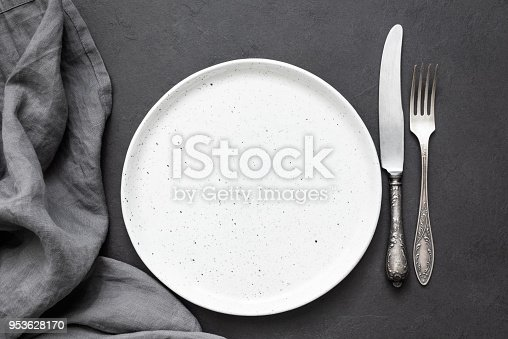 Vintage cutlery or silverware, empty plate and kitchen textile napkin. Top view, copy space for text