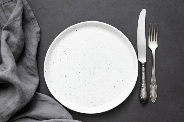 Vintage cutlery or silverware, empty plate and kitchen textile napkin stock photo