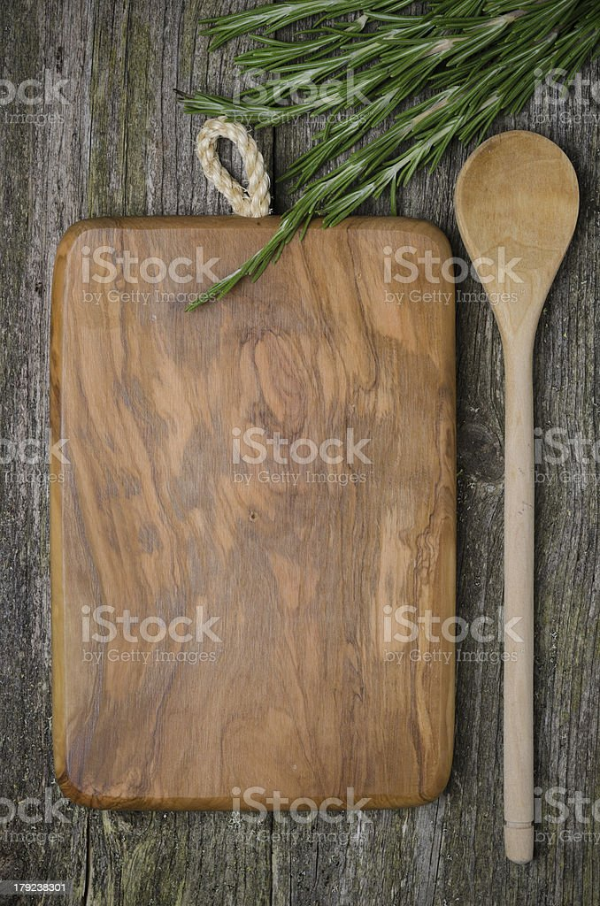 vintage cutting board with space for text, spoon fresh rosemary royalty-free stock photo