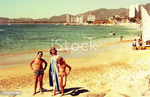 Vintage image of a mother and her children at the beach.
