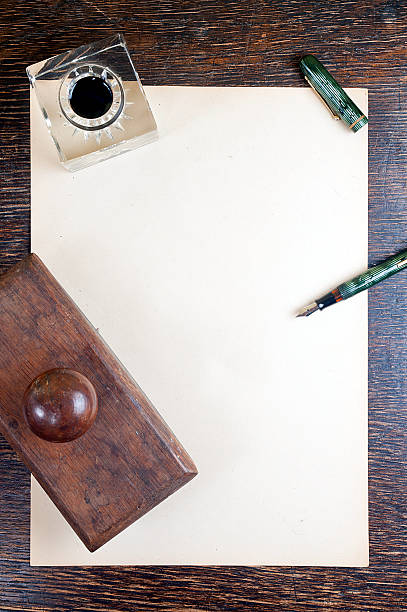 Vintage desk and paper Top view of old yellowed sheet of paper at wooden vintage desk. fountain pen, inkstand with black ink and blotting paper. blotter stock pictures, royalty-free photos & images