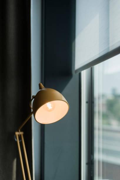 vintage schreibtischlampe in industriellen fensterrahmen. - bürolampe stock-fotos und bilder