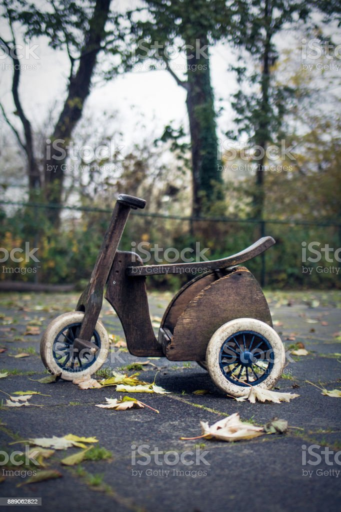 Vintage diy tricycle toy at outdoors rainy autumn playground stock photo