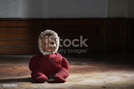 A DSLR photo of a vintage and damaged doll sitting on a parquet floor in a dark room of an abandoned house. The doll features red clothes and a baby hat. It has a missing eye. Light comes from a window at the right side. Front view.