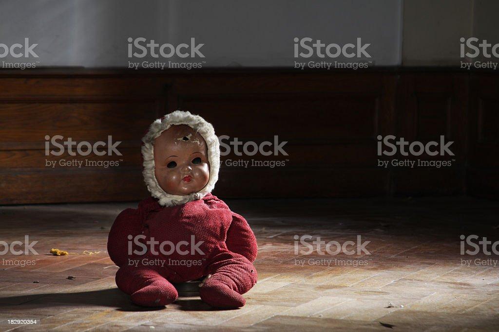 Vintage doll on parquet floor in a dark room stock photo