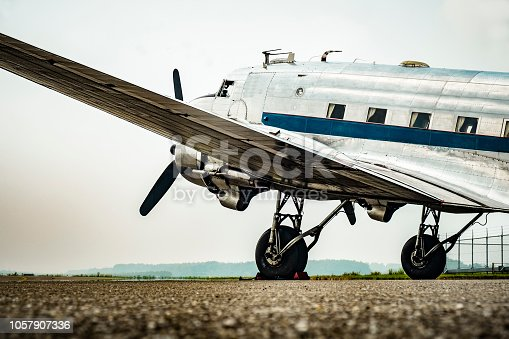 Vintage Douglas DC-3 Dakota propellor airplane ready for take off at the runway of an empty airfield. Image with a retro look.