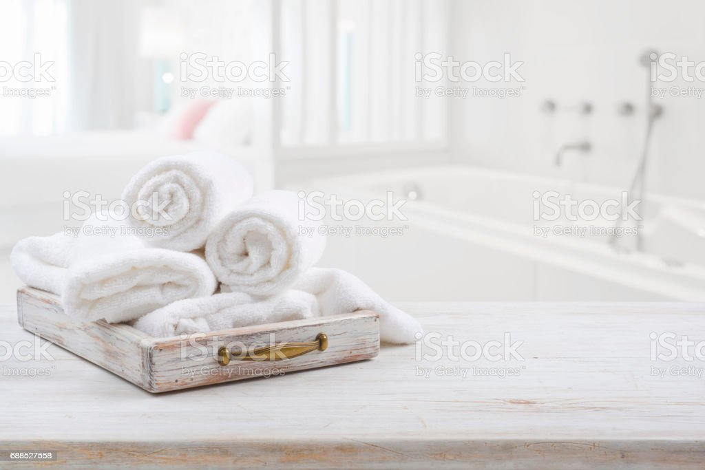 Vintage drawer with white towels over blurred bathroom and bedroom stock photo