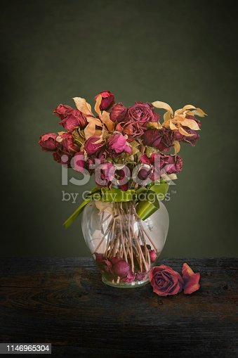 Vintage dried red roses flowers in a glass vase with green ribbon