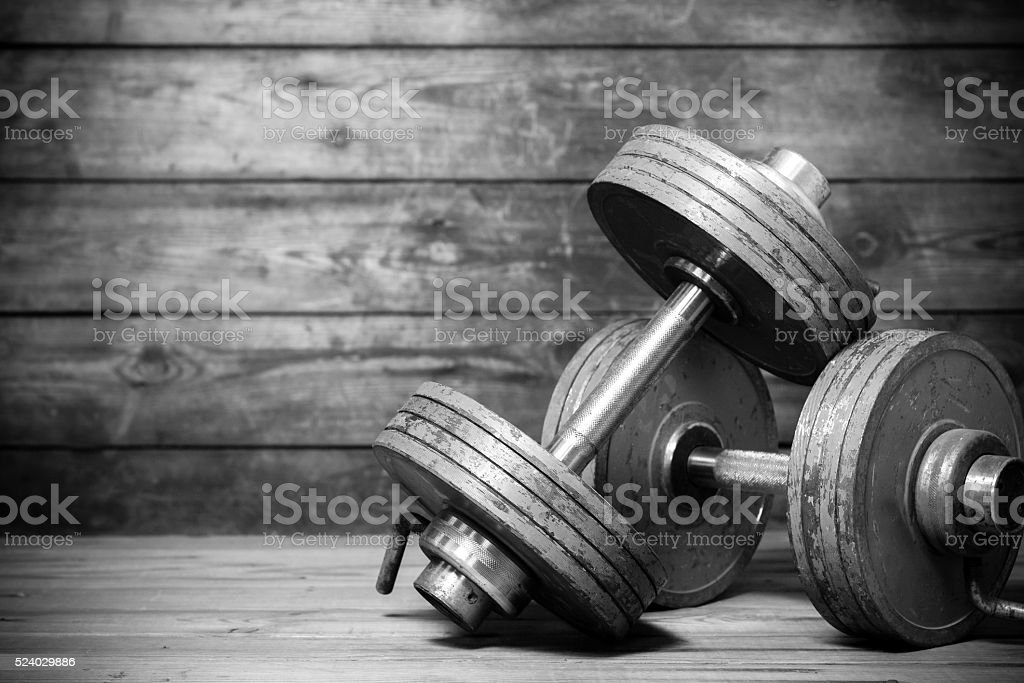 Vintage dumbbells on the wooden floor. stock photo